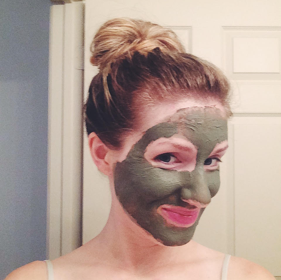 Woman smiling and wearing green clay mask on her face