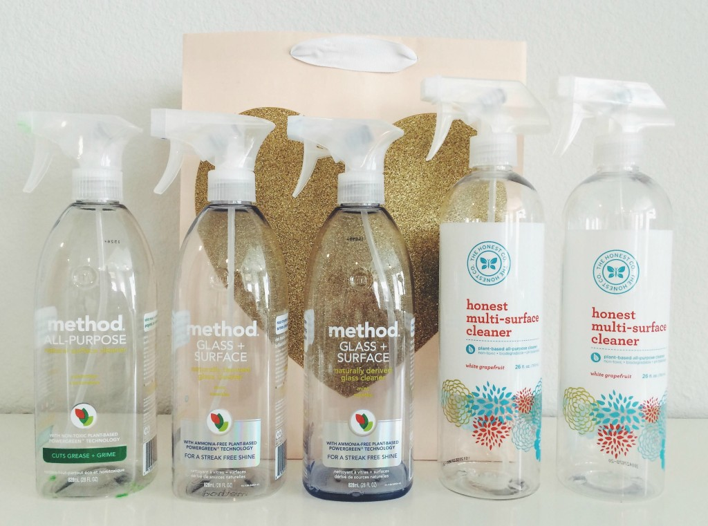 Empty cleaning product bottles lined up in front of blush and gold heart gift bag