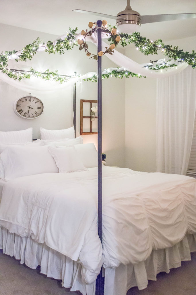 black canopy bed with white bedding and fairy lights on top