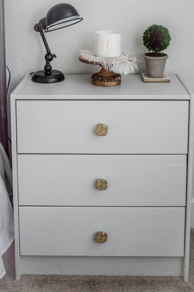 light grey night stand with candle and decor on top