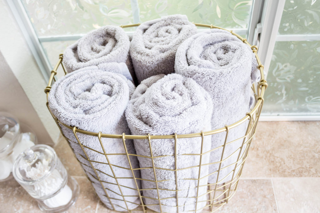 grey towels rolled up in gold basket in master bathroom