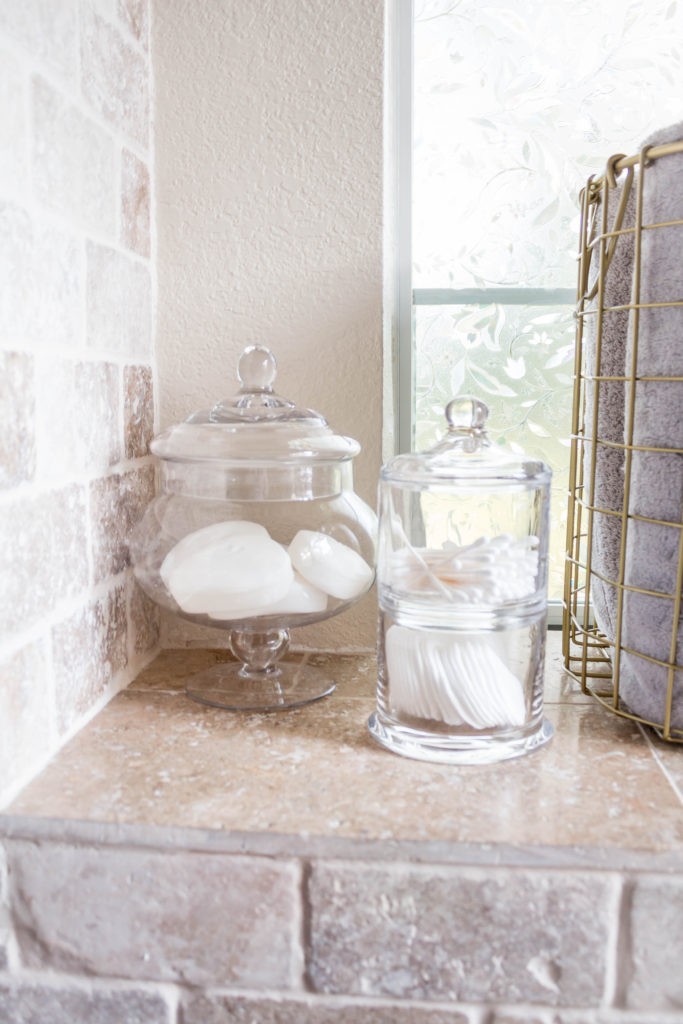 glass apothecary jars with bathroom items in master bathroom