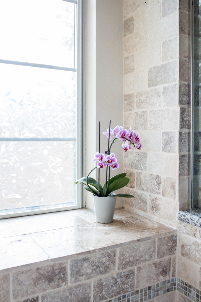 purple orchid on bathroom windowsill in master bathroom