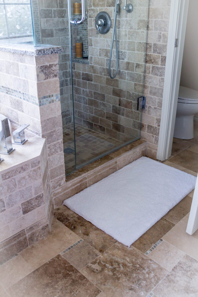 white bath rug outside of shower in master bathroom