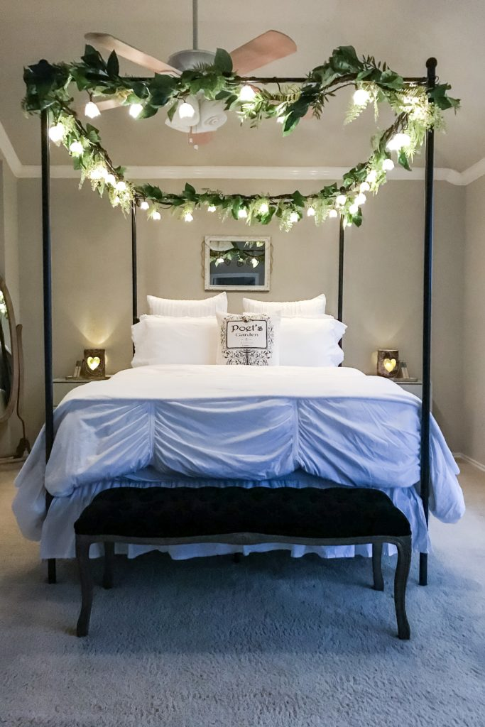 black canopy bed in bedroom with flower fairy lights hanging on top