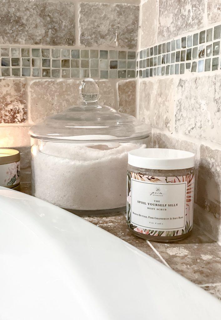 pink bath salts in glass jar and body scrub