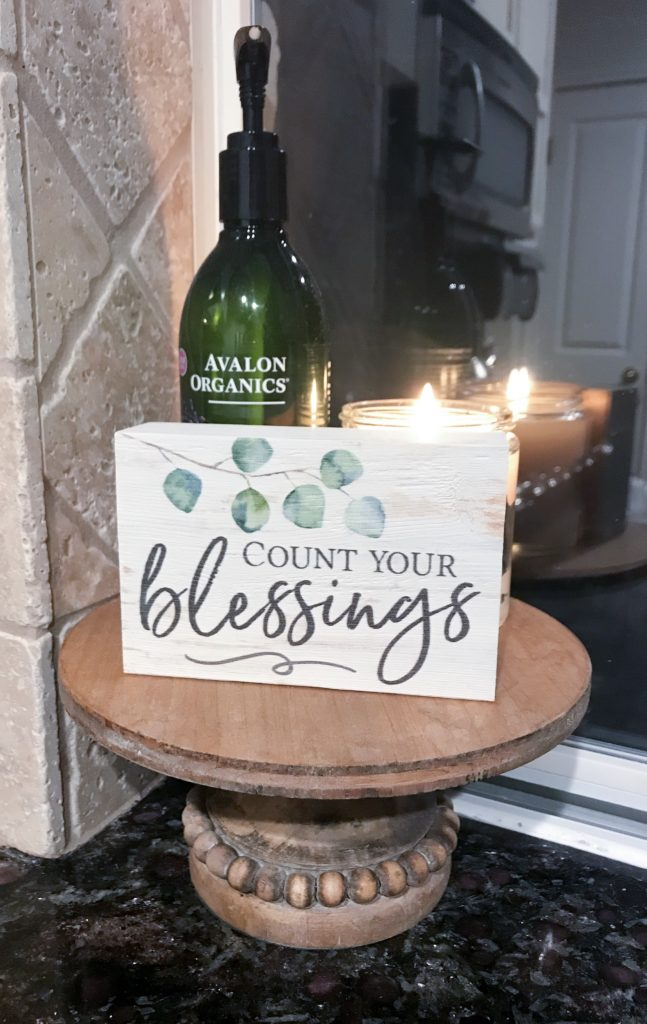 Candle burning on stand by sink with lotion and decorative sign