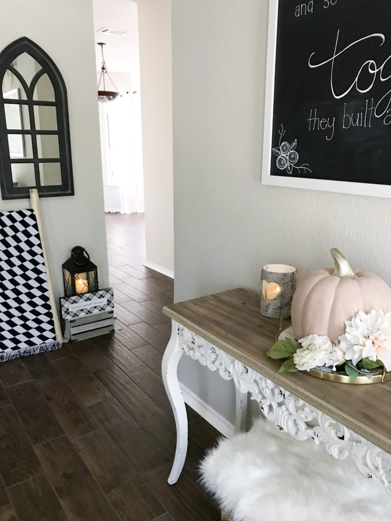 entryway to home with table and pink pumkpin