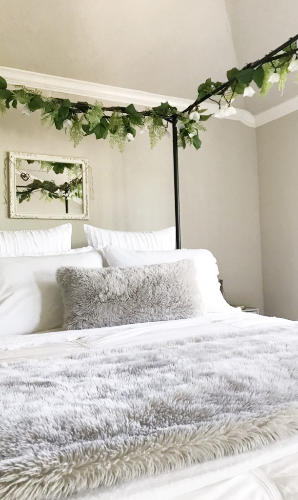 canopy bed with greenery on it and light grey faux fur pillows on bed for my fall tour