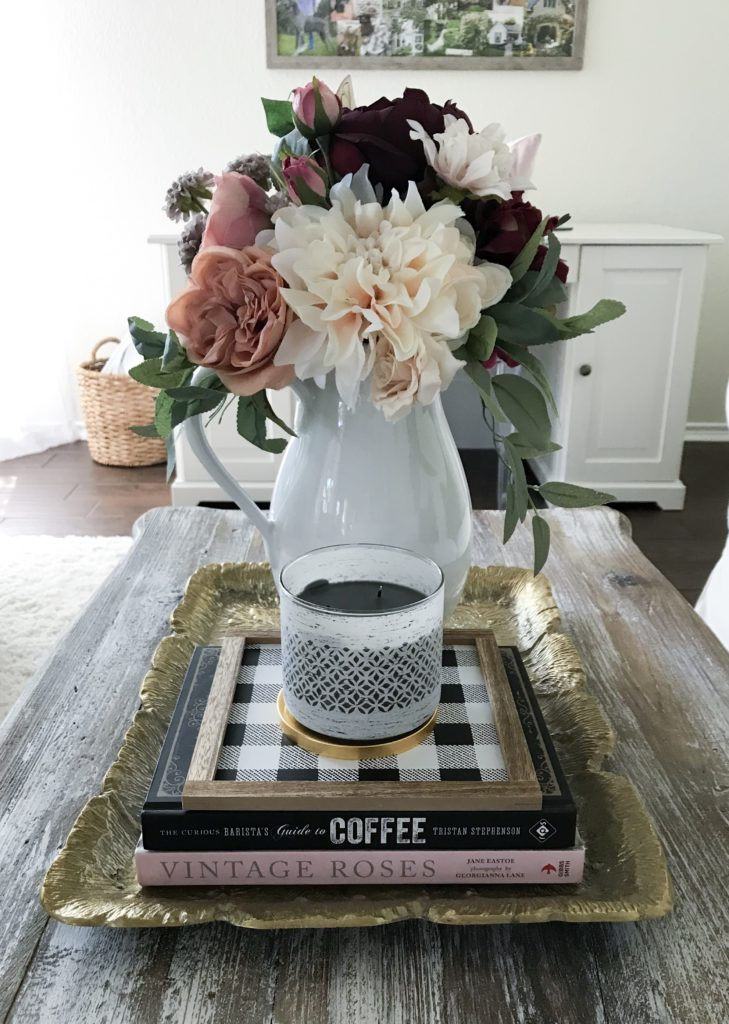 coffee table with books on gold tray and candle and white pitcher with faux flowers in it