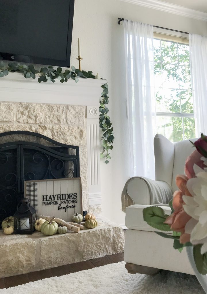 fireplace with fall sign and pumpkins on it and wingback chair by the side for my fall tour