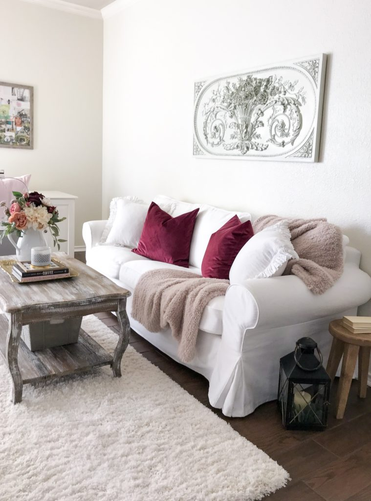 white couch with pink blanket and berry pillows under a french wall art piece